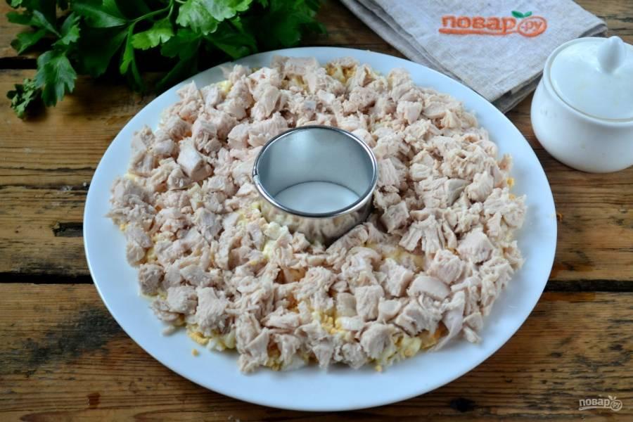 Сверху выложите измельченную куриную грудку и также смажьте майонезом.