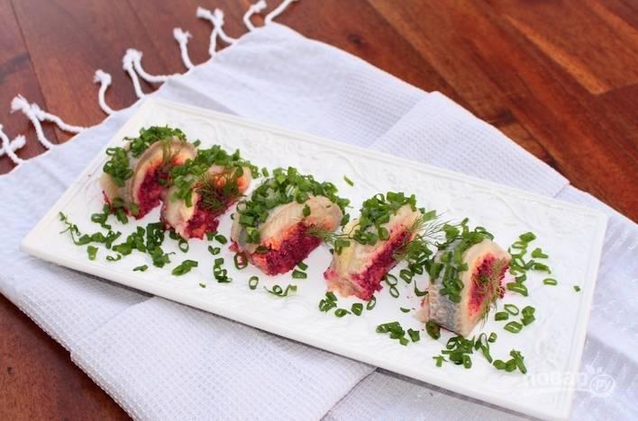 """Перед подачей """"Селёдку под шубой"""" разрежьте на части. Украсьте блюдо нарезанным зелёным луком. Приятного аппетита!"""