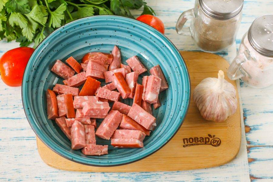 Копченую колбасу любого сорта нарежьте брусочками и высыпьте нарезку в миску или салатник.