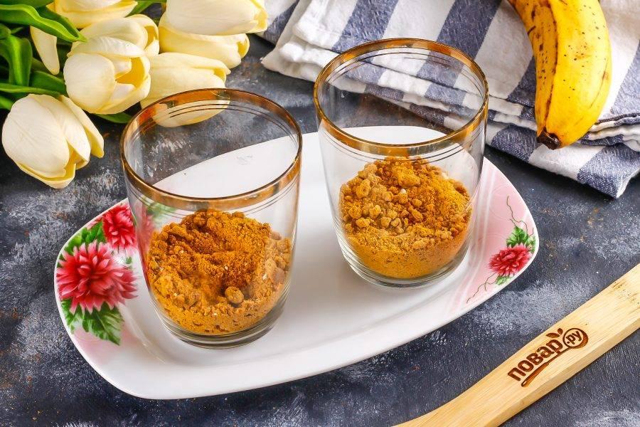 Разделите песочную крошку на две части и одну из них еще разделите на два. Всыпьте в стаканы, чашки или пиалы. Крошку можно приготовить из любого песочного печенья, остатков коржей и т.д.