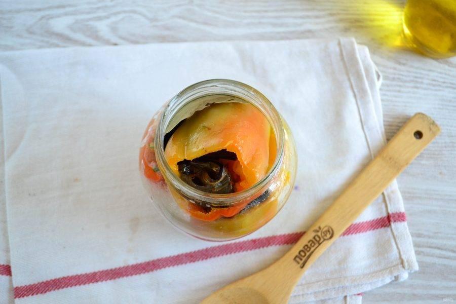 В бланшированные перцы положите по 2-3 рулетика из баклажанов (в зависимости от размера перца). Сложите фаршированные перцы в банку. Туда же положите пару лавровых листиков, можно также несколько горошин черного перца.