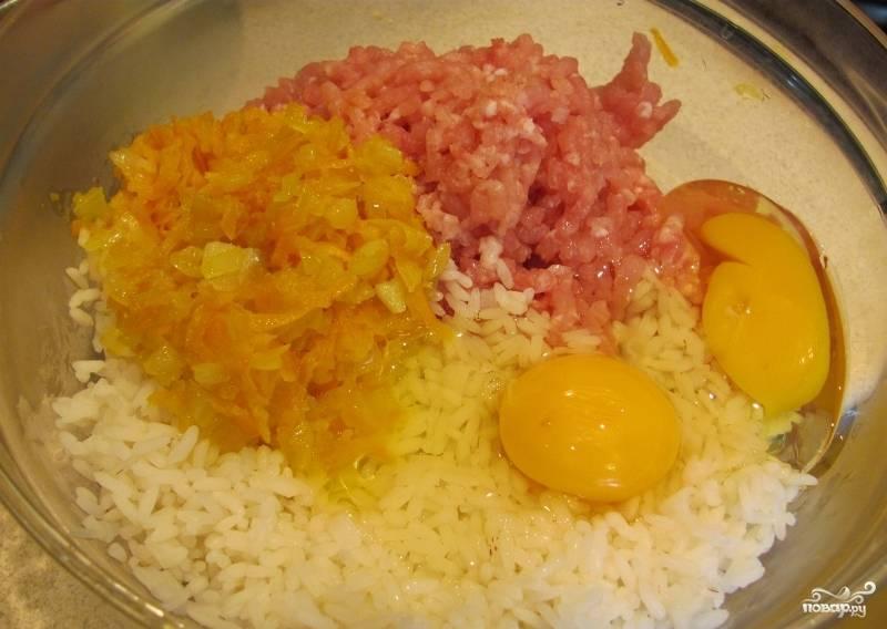 Теперь в миску с фаршем добавляем половину обжаренных овощей, два яйца, рис, солим и посыпаем перцем. Тщательно перемешиваем все ингредиенты.