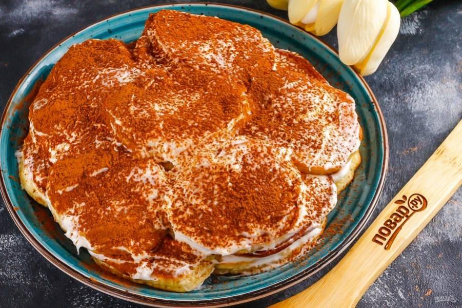 Присыпьте приготовленный торт какао-порошком и поместите в холодильник на 1-2 часа для пропитывания.