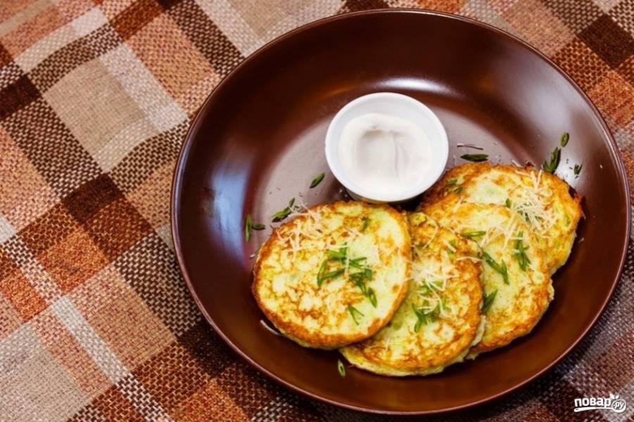 4.Готовые драники сперва перекладываю на бумажное полотенце, чтобы ушел лишний жир, затем кладу на тарелку, посыпаю зеленью и тертым сыром и подаю со сметаной.