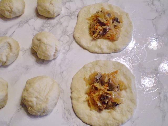 11. Тесто сразу делим на части, количество частей на ваш вкус, сегодня я делала относительно большие пирожки, поэтому разделила на 12 частей. Муку больше не используем. Берем масло растительное, протираем стол и руки. Каждый кусочек теста растягиваем пальцами, придавая форму круга. Кладем начинку на середину. Залепливаем край.