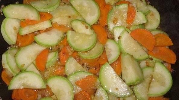 Обжарить лук до прозрачности, а затем добавить морковь и кабачки.