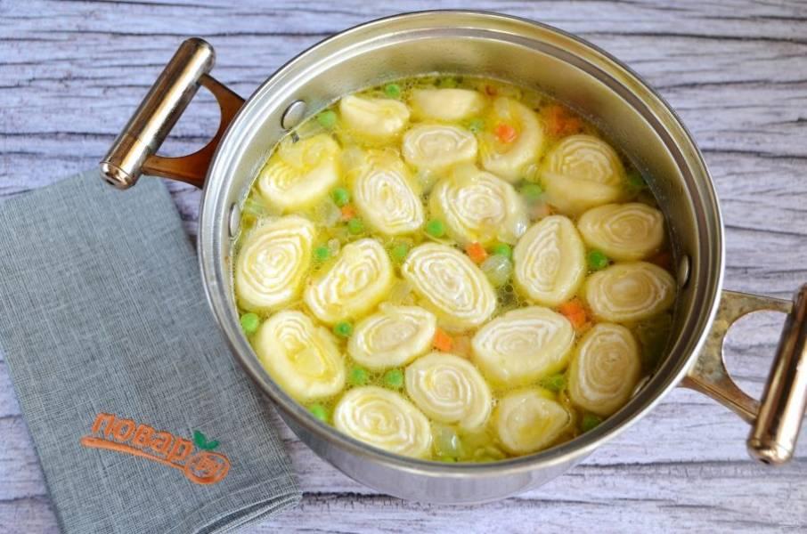 11. Положите в суп жареные овощи, рулетики, горошек и варите 5-7 минут.