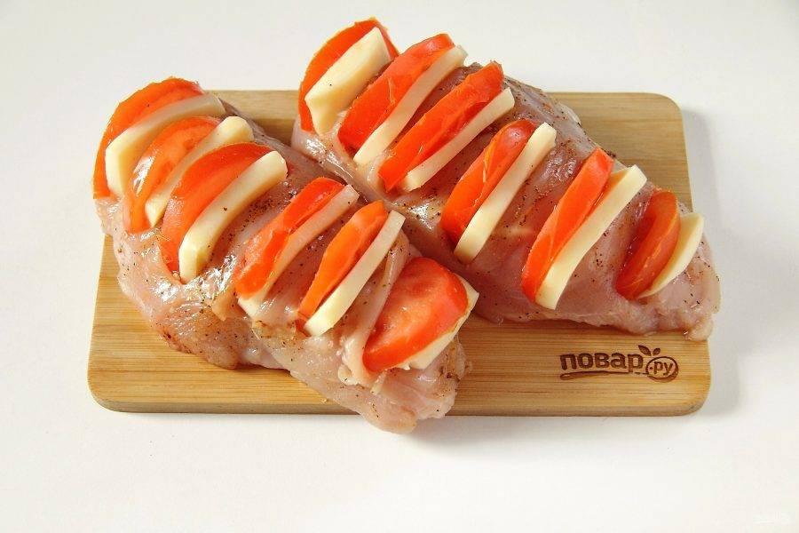 В каждый надрез вставьте по ломтику сыра и кружочку помидора. Если помидоры крупные, разрежьте кружочки пополам.