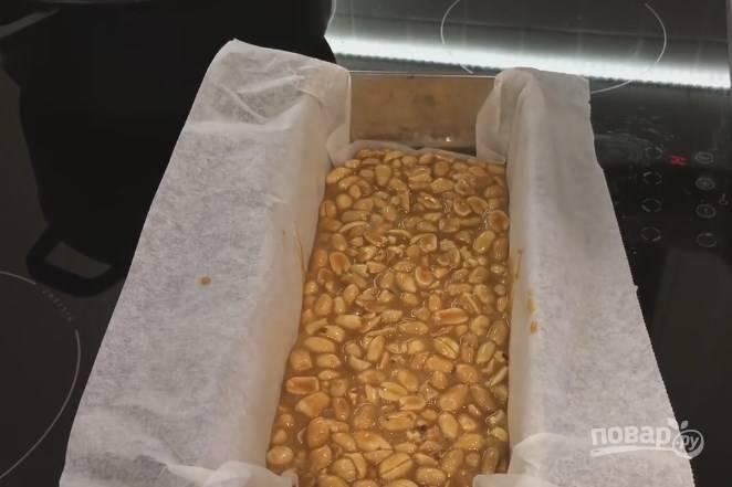 6. В карамель отправьте подсушенный в духовке арахис и перемешайте. Форму, в которой будете делать торт, застелите пергаментом и вылейте на дно карамель. Поставьте форму в холодную воду.
