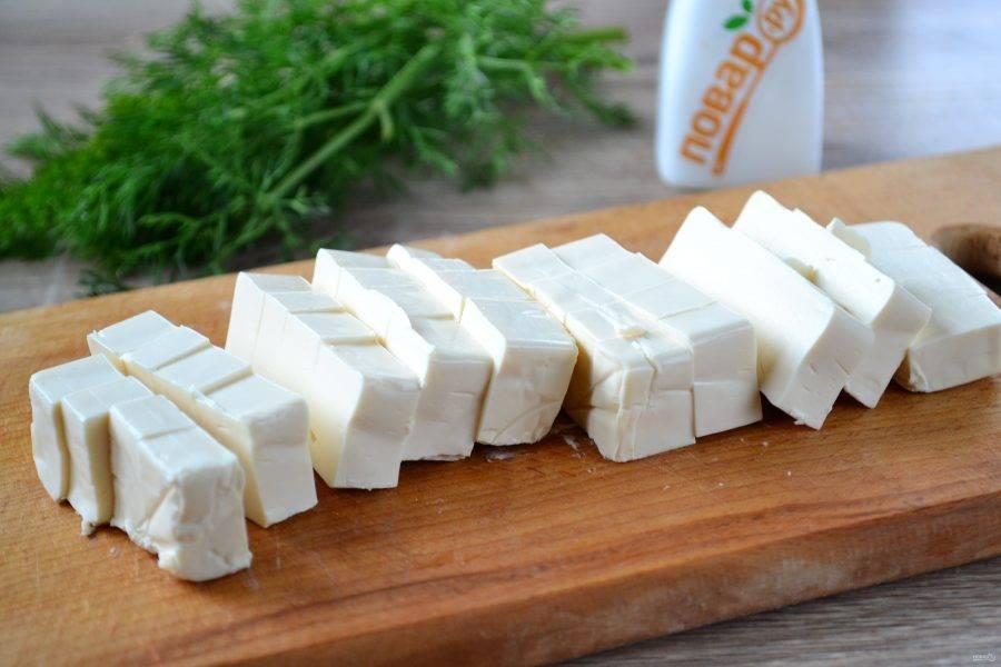Плавленные сырки нарежьте небольшими кубиками, чтобы они быстрее расплавились в супе.