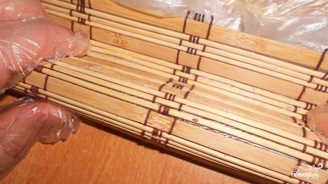 5. Бамбуковую дорожку оберните пищевой пленкой. Выложите на нее лист нори. Смочите руки. Возьмите порцию риса и разместите ее сверху нори, отступив немного от края.