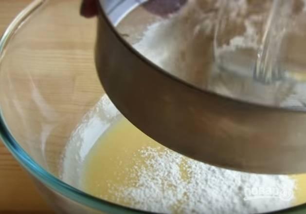 2. В несколько приемов просейте муку с разрыхлителем в масляную смесь и замесите тесто. Оно будет немного крошиться.