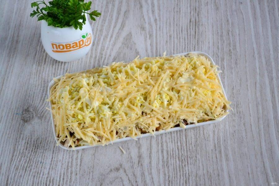 На мелкой терке натрите твердый сыр и выложите на салат сверху и по бокам.