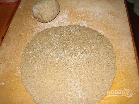 Замешиваем тесто из просеянной муки, соли, воды и масла. Скатываем его в шар, заворачиваем в пленку и оставляем на минут 30 в покое. Затем раскатываем тесто в форме овала толщиной 0,5 см. Выложим на пергамент, который выложим на лист фольги.