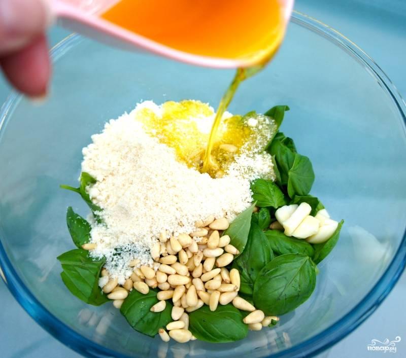 Шаг 1. Смешайте в миске базилик, кедровые орешки, пармезан, чеснок, оливковое масло и соль.