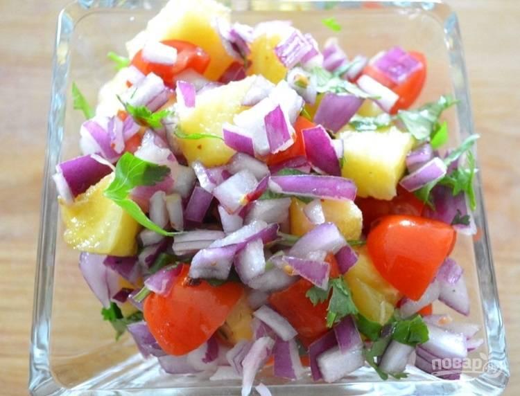 3.Нарежьте кусочками ананас, красный лук, черри, кинзу и хлопья красного перца, добавьте сок одного лайма и перемешайте.