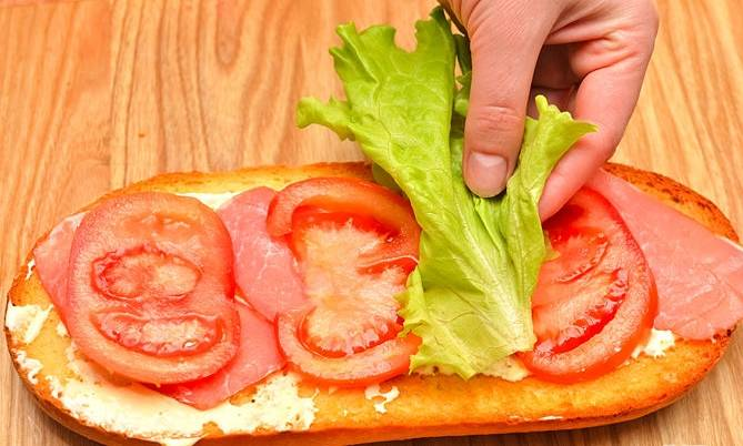 Уложите слой курицы, помидоры и лист салата.