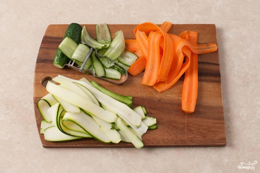 При помощи овощечистки тонкими пластинами вдоль нарезаем огурец, цукини до семян (семена не нужны) и очищенную от кожуры морковь.