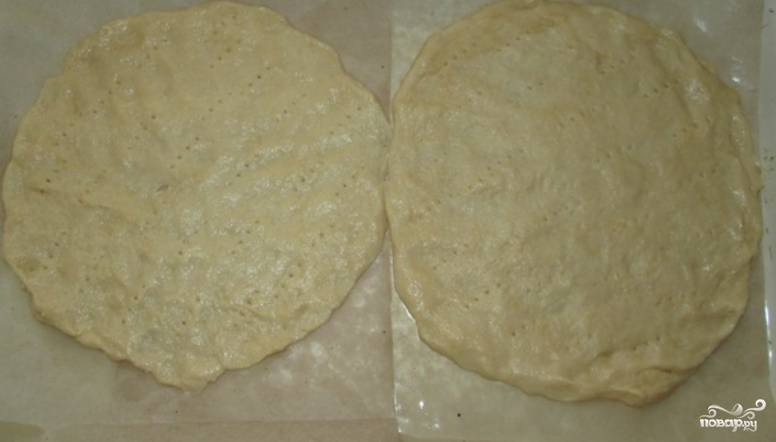 Тесто разминаем и раскатываем, формируем из него 5 одинаковых коржей. Выкладываем их на противень, застеленный бумагой для выпечки. Делаем в тесте проколы вилкой.