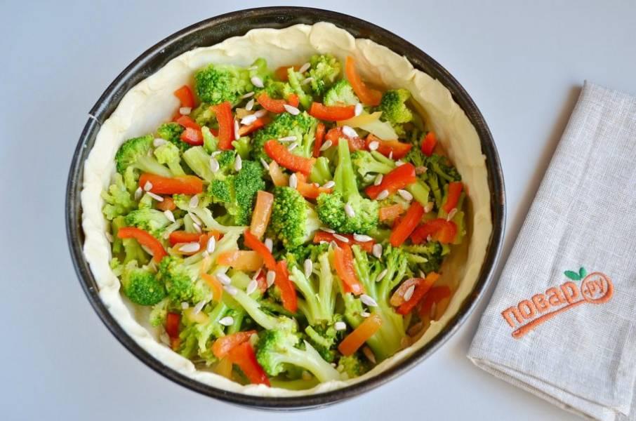 6. Форму застелите пергаментом, тесто раскатайте и уложите в форму, формируя высокие бортики. Распределите брокколи, болгарский перец, посыпьте семечками или орешками.