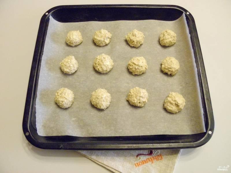 Подготовьте противень, застелите его бумагой для выпечки. Чайной ложкой набирайте тесто и влажными руками формируйте шарики. Выкладывайте их на лист на расстоянии друг от друга.