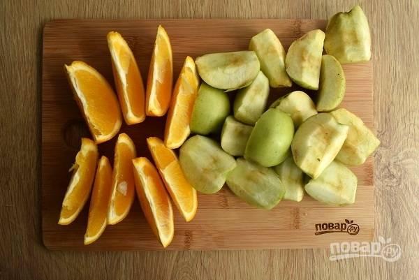 Яблоки нарежьте на четыре части, удалите сердцевинку и семена. Апельсин нарежьте ломтиками, удалите у него косточки.