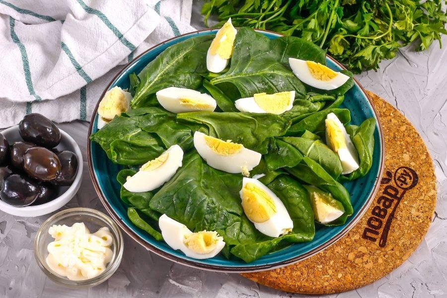 Очистите отварные куриные яйца от скорлупы, нарежьте четвертинками и выложите на тарелку.
