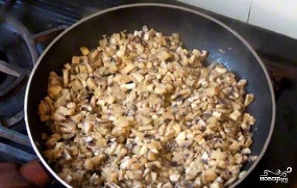 Добавляем к луку грибы, жарим 7 минут.