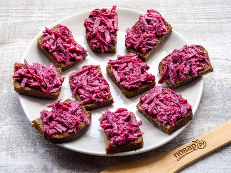 Порционные куски хлеба разрежьте на половинки и выложите на них свеклу.