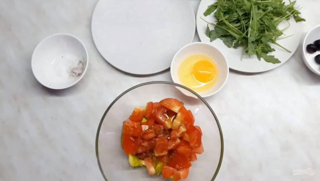 2. Помидор нарежьте такими же кусочками, не снимая с него кожуру, и добавьте к авокадо. Туда же добавьте оливковое масло, посолите и поперчите, отставьте на несколько минут для мариновки.