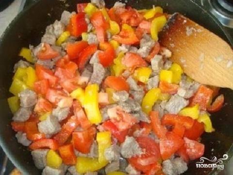 2.Мясо можно нарезать маленькими кубиками или использовать фарш. Овощи нужно вымыть и почистить. Перец нарежьте небольшими кусочками и слегка обжарьте на сковороде. Вытащите перец в отдельную посуду и обжарьте мелко нарезанный лук. Добавьте мясо и обжарить его почти до готовности. Помидор очистить от кожицы и мелко нарезать. Обжаренный перец и нарезанный помидор добавить в мясо, перемешать.