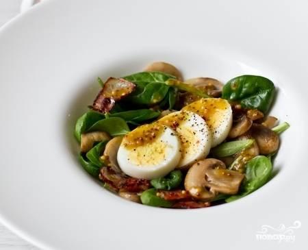 В порционные тарелки разложите шпинат, пожаренный бекон, грибы и нарезанные ломтиками яйца. Полейте салат заправкой и подавайте на стол. Приятного аппетита!
