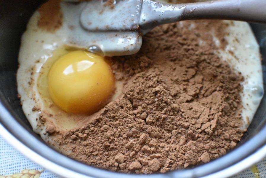Для крема хорошо размешайте в антипригарной кастрюльке желток со второй половиной банки сгущенного молока и какао-порошком.