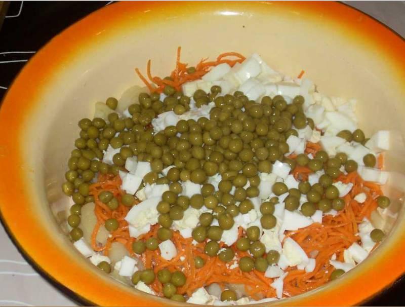 2. Дальше добавим измельченные отварные яйца, морковку по-корейски и горошек. Тоже немного смажем майонезом.