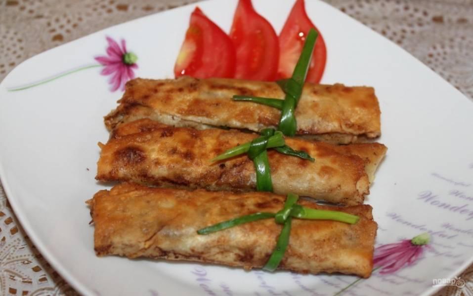 9.Выкладываю трубочки на тарелку, обвязываю перьями лука и подаю горячими со свежими овощами.