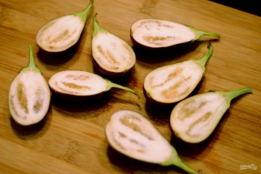 2.Разрежьте каждый баклажан пополам. Если используете крупные овощи, нарежьте крупными кусочками.
