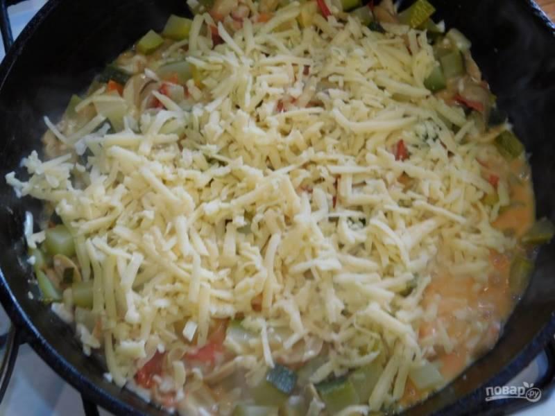 Добавьте соль и специи по вкусу. Посыпьте тертым сыром, перемешайте и снимите с огня. Дайте блюду постоять еще пару минут под крышкой, чтобы сыр расплавился.