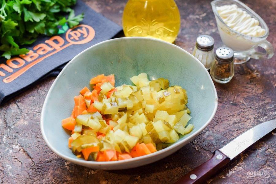 Соленые огурцы нарежьте небольшими кубиками и добавьте в салат.