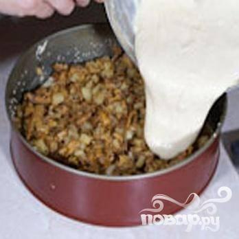 5.Смазать маслом форму для выпечки и посыпать кунжутом или мукой. Половину теста выложить, распределить начинку сверху, накрыть оставшимся тестом начинку.