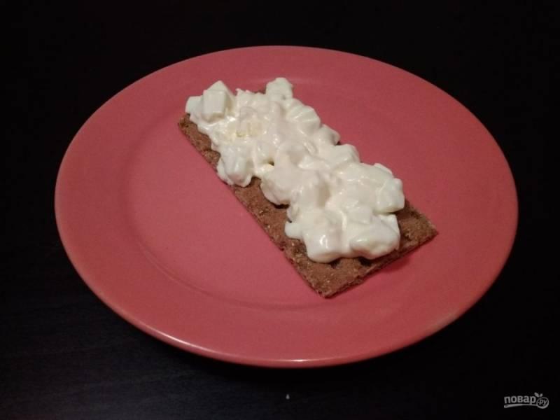 8. Заранее отварите яйцо. Потом мелко его нарежьте и перемешайте с оставшимся соусом. Выложите салат на хлебец.