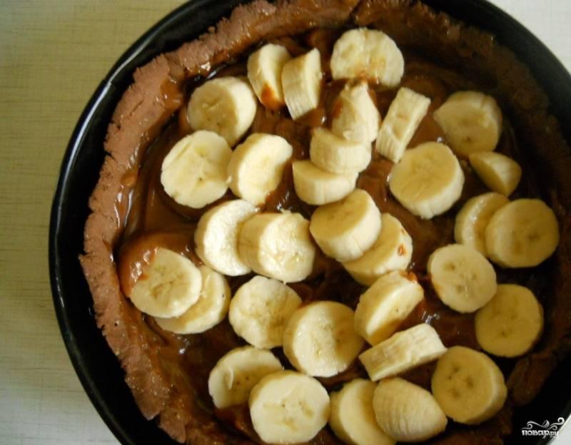 Когда форма из теста выпечется, достаньте ее из духовки и остудите. Откройте банку сгущенки, вылейте ее содержимое в форму. Очистите бананы, нарежьте их кружочками. Выложите бананы на сгущенку.
