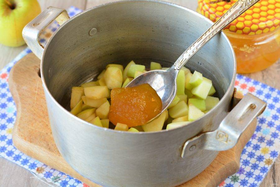 Яблоки сложите в кастрюлю, полейте медом, добавьте воду и варите варенье 15 минут на медленном огне.