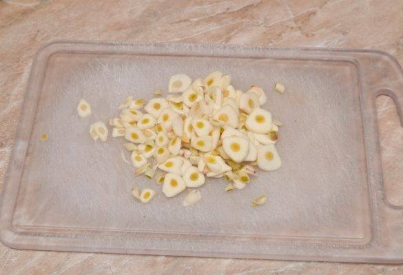 Чеснок также очистим и нарежем тонкими пластиками.