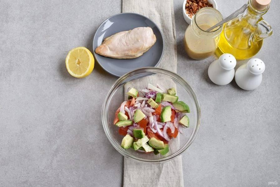 Помидоры нарежьте на четвертинки, удалите семена и нарежьте кусочками. Выложите в удобную миску. Тонко нашинкуйте лук и добавьте в миску к помидорам. Авокадо разрежьте пополам, удалите косточку, снимите шкурку и нарежьте небольшими ломтиками. Сбрызните авокадо чайной ложкой лимонного сока, чтобы мякоть не потемнела. Выложите в миску.