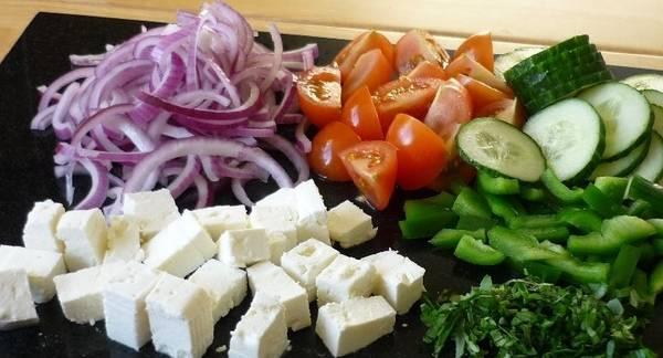 Овощи тщательно промойте. Затем порежьте кружочками огурец, кубиками - фету, лук - полукольцами, помидоры и перец - мелкими кусочками. Смешайте все ингредиенты в одной емкости.