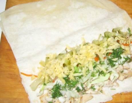 Разложите лист лаваша, внутрь выкладываем мясо, капусту, корейскую морковку, огурцы, зелень и сыр.