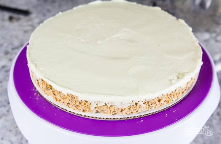 21.Выложите на тарелку один корж, щедро смажьте его белым кремом.