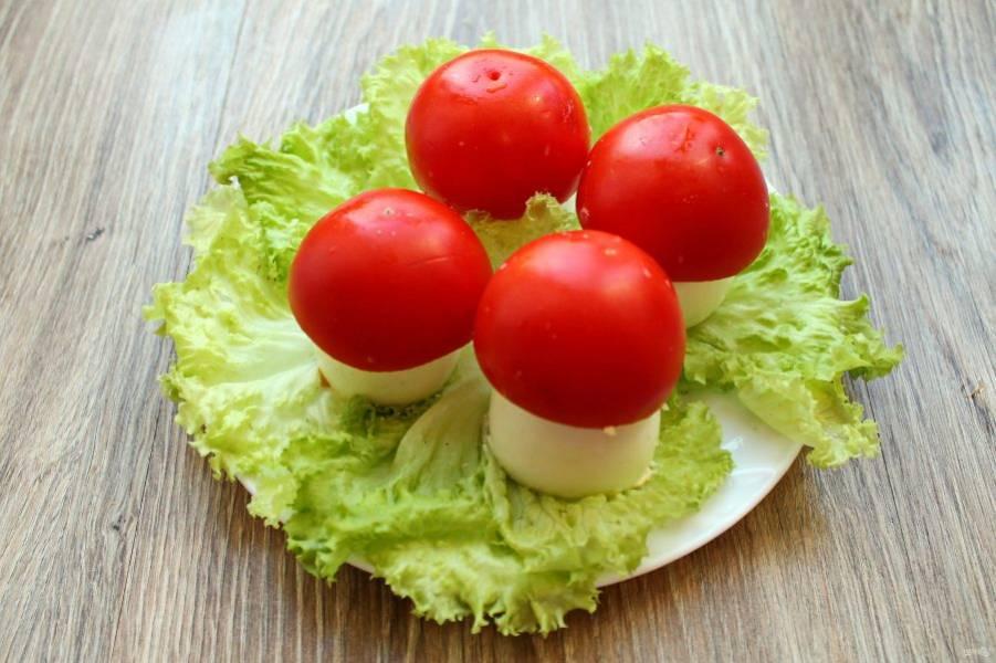 Установите шляпки поверх фаршированных яиц.