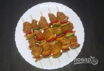 Когда все замаринуется, нанизайте мясо попеременно с перцем и луком на деревянные шпажки.