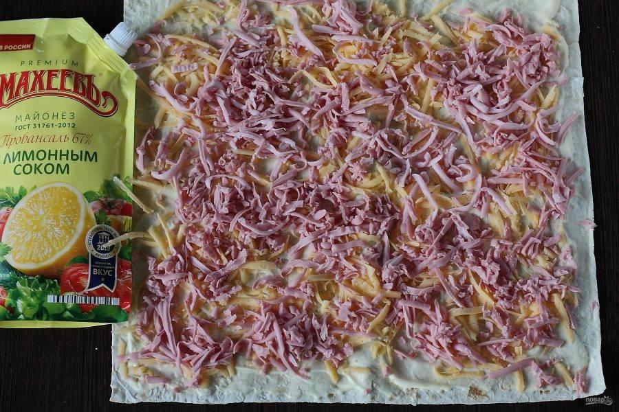 Смажьте лаваш майонезом, посыпьте тертым сыром и тертой на крупной терке колбасой.
